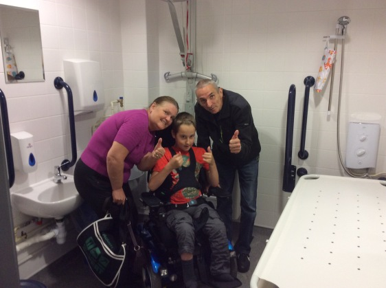 Adam is using his powered wheelchair and is posing with his grandparents in the new Changing Places toilet at Cornwall Services. They are all smiling and have their thumbs up. The changing table, shower, hoist and basin are visible around the family.