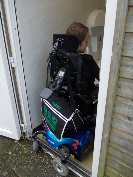 Boy using an adult sized powered wheelchair is unable to get in the disabled toilet with the whole of his chair. The rear castors are still outside the room. The chair is blue and the boy is visibly sad.
