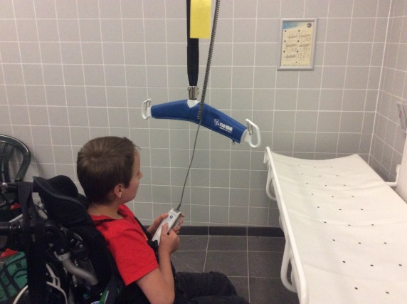 A child using a wheelchair is operating a ceiling hoist. An adult sized changing table is also shown.