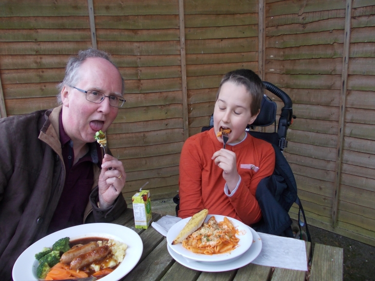 Adam and Daddy eating lunch outdoors. Both are posing with open mouths and forks of food. Adam has penne pasta with garlic bread. Daddy has bangers and mash.