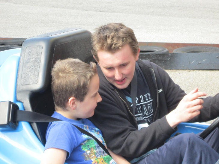 Adam and his big brother sat in a Go Kart.