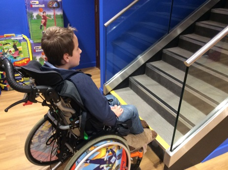 Ten year old boy, sat in his wheelchair, looking sadly at a flight of steps in a toy shop.