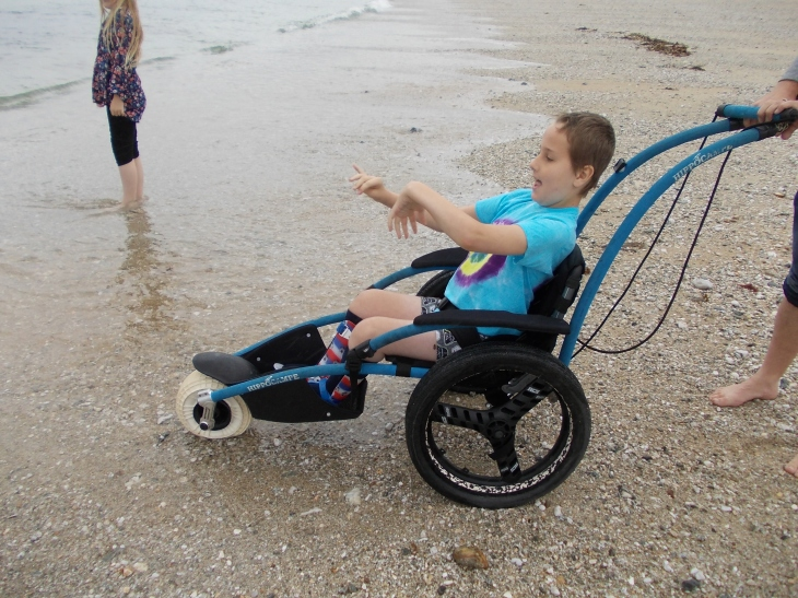 Child using an all terrain wheelchair, at the beach, getting closer to the see. He is waving his arms and looking excited.