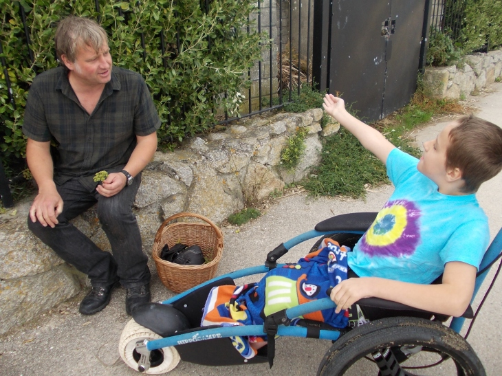 Child sat in an all terrain wheelchair looking intently at a man holdinga plant a basket of foraged goodies.