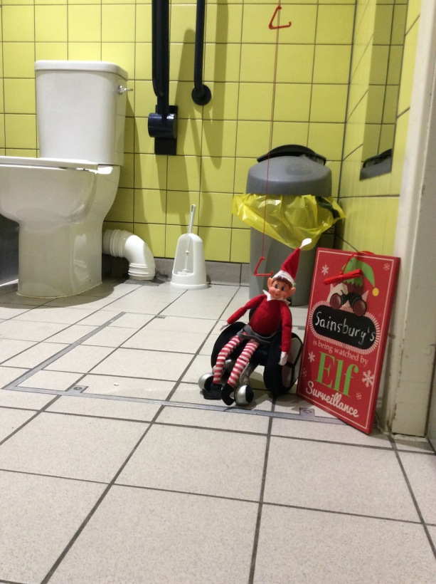 "Elf in wheelchair next to a sign saying ""Sainsburys is being watched by Elf Surveillance""."