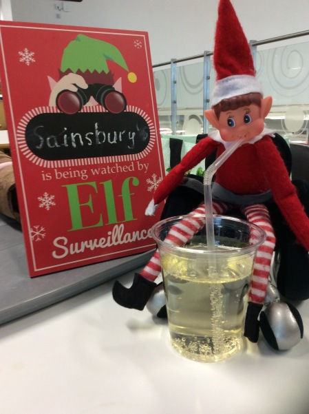 "Elf toy, sat in a wheelchair, drinking a drink besides a sign saying ""Sainsbury's is being watched by Elf Surveillance""."