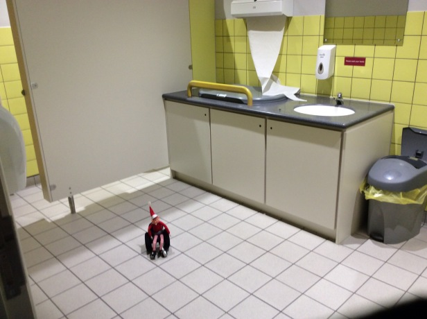 Toy Elf in wheelchair, looking at baby changing room.