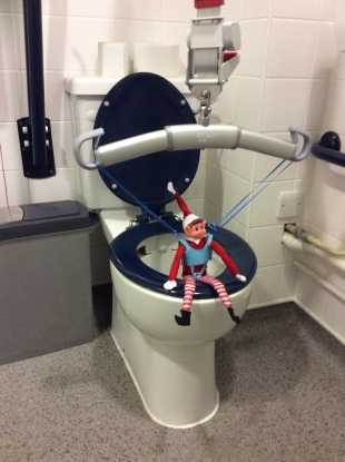 Alfie the Elf, sat on the toilet, using the hoist and his toileting sling.