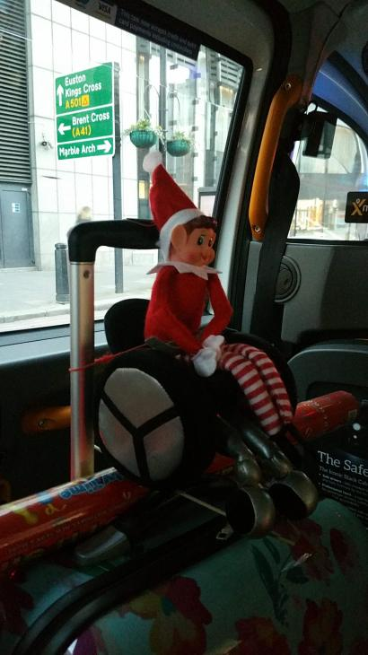 Toy Elf, sat in his wheelchair, riding in a London taxi.