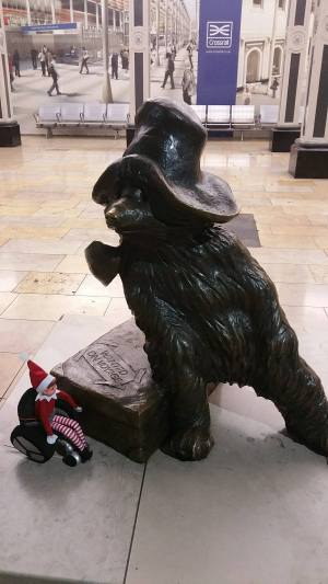 Toy Elf in wheelchair next to a statue of Paddington Bear.