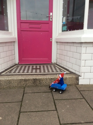 Toy Elf in powered wheelchair looking up a step to an icecream shop.