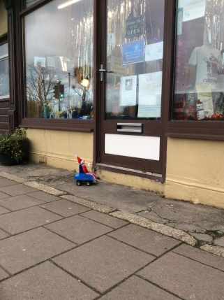 Toy Elf in powered wheelchair unable to get up a step into a gift shop.