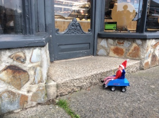 Toy Elf in powered wheelchair sat outside a bakery due to a step to the doorway.