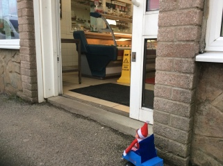 Toy Elf in a powered wheelchair unable to access a food store due to a step.