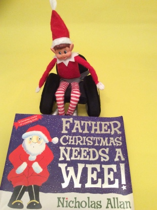 "Alfie the Elf, sat in his wheelchair, with the book ""Father Christmas Needs A Wee"" in front of him."