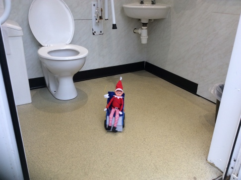 Toy Elf in a toy powered wheelchair, on the floor of a disabled toilet.