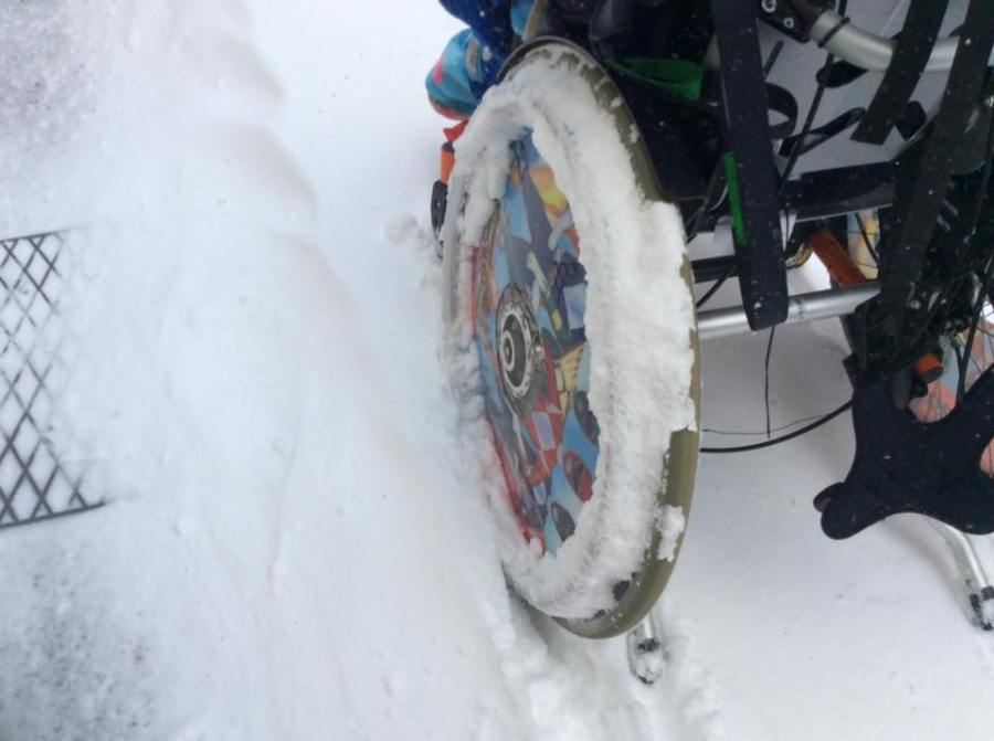 Rear view of a wheelchair in the snow, with the focus being the wheel of the chair absolutely covered with snow to a point where the push rim is no longer visible.