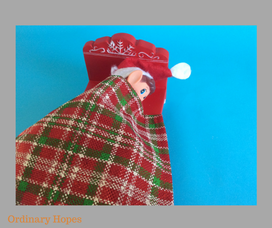 Elf in a red bed, with a tartan blanket hiding his nose and mouth. Eyes are open.