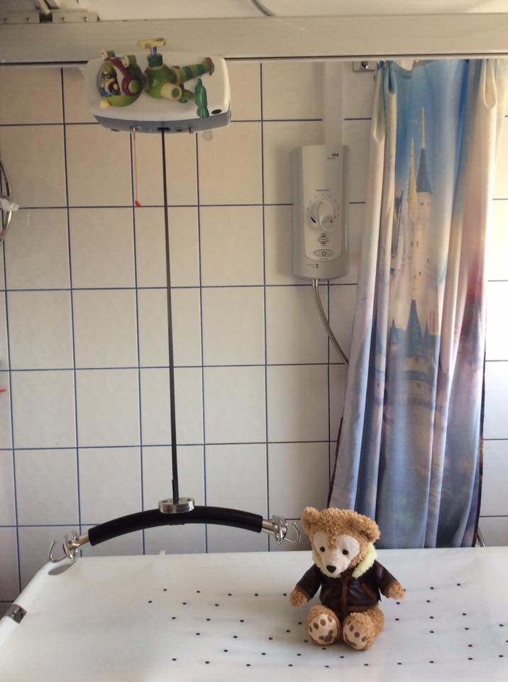 Photo showing a ceiling hoist and changing table. There is a bear wearing a jacket on the bench.