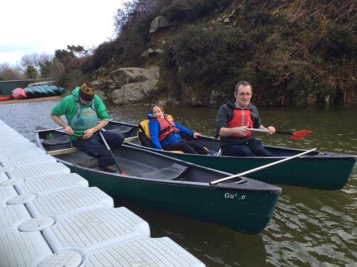 Adam with his PA and instructor from BF Adventure. They are using two canoes joined together by three wooden bars to add stability. Adam is wearing a red life jacket and sat on a big comfy yellow seat for support. It is a grey day and everyone is dressed warmly.