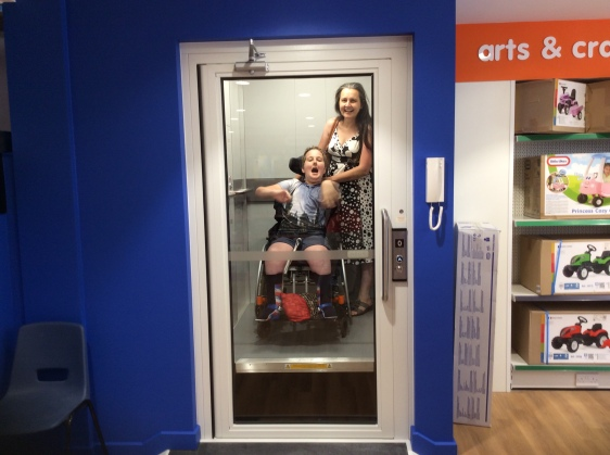 Wheelchair using child and his mum in a lift in a toy shop. The child is wearing blue shorts and a t-shirt shirt with Hogwarts Castle on it. Mum is wearing a black and white summer dress. The child is open mouthed and waving his arms in excitement. Mum is smiling widely.