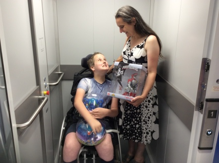 "Wheelchair using child and his mum in a lift after shopping for toys. The boy is carrying two toys from the ""Miles from Tomorrowland"" show. Mum is carrying a Power Rangers T-Rex Zord. They are both smiling widely and looking at each other lovingly."