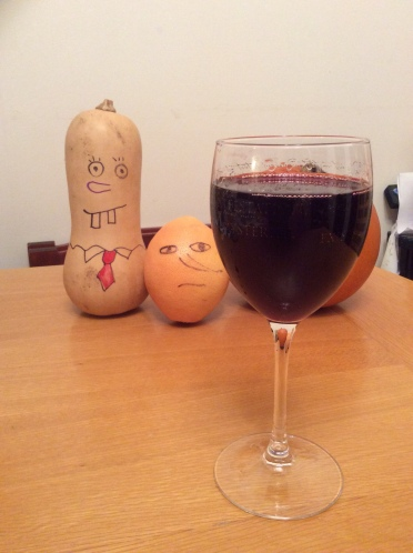 Glass of red wine in the foreground. Behind it is a butternut squash and a grapefruit, both of which have faces drawn on them. The butternut squash has two big gappy rectangular teeth, a big nose, round eyes, and a shirt collar with a red tie. He resembles Spongebob Squarepants. The grapefrui looks sternm with oval eys, a serious mouth and a big pointy nose.