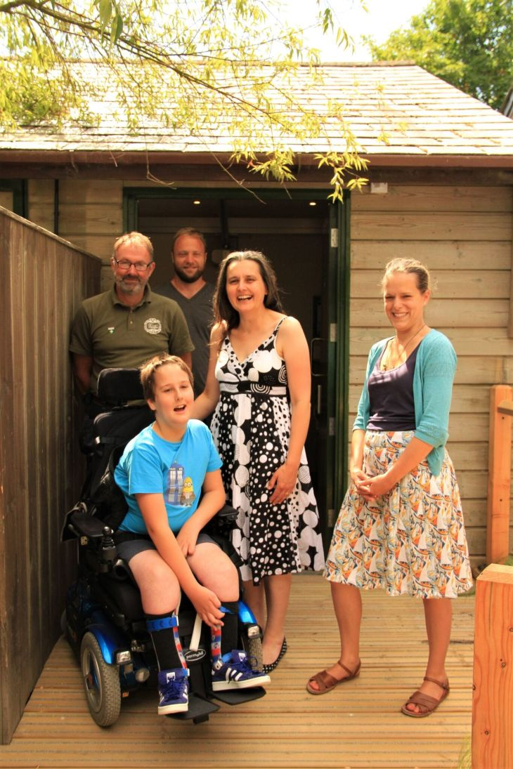 Adam is using his blue powered wheelchair and is outside the Changing Places toilet with his mum, and with two men and a woman from Heligan who all made the facility happen. Adam is wearing shorts and a bright blue T-shirt and looks very happy.