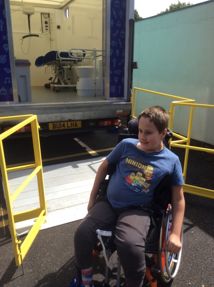 a smiling boy, wearing a blue t-shirt with Minions dressed as The Big Bang Theory characters, sat on his orange powered wheelchair. Behind him is a van with the tail lift down. Inside the van a toilet with rails, an adult sized changing table and ceiling hoist are all visible.