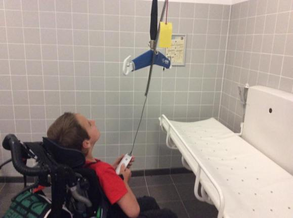 A boy of about 10 years old, wearing a red shirt and using a manual wheelchair, is sat in front of a white changing table and is operarting the ceiling hoist.