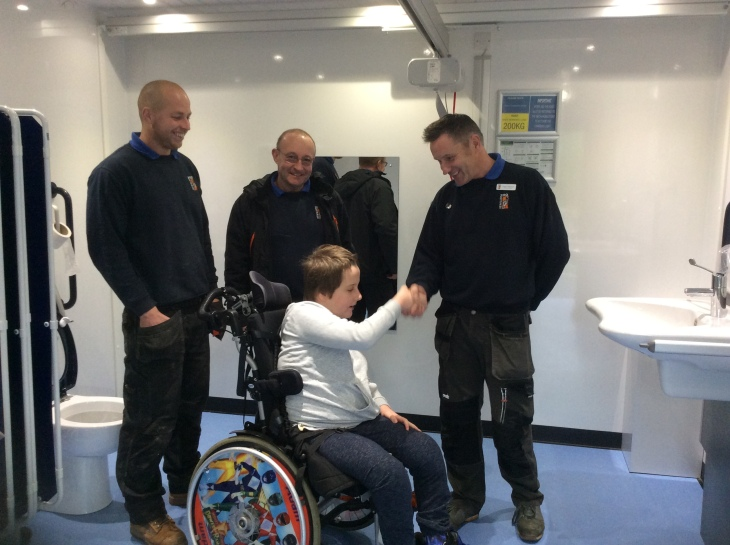 Three men wearing Newquay Zoo uniforms are standing inside the Changing Places toilets. A boy is shaking hands with one of them. The boy is wearing a light grey hooded top and dark grey trousers. He is using a manual wheelchair with Power Rangers on the wheels. All of them look very happy.