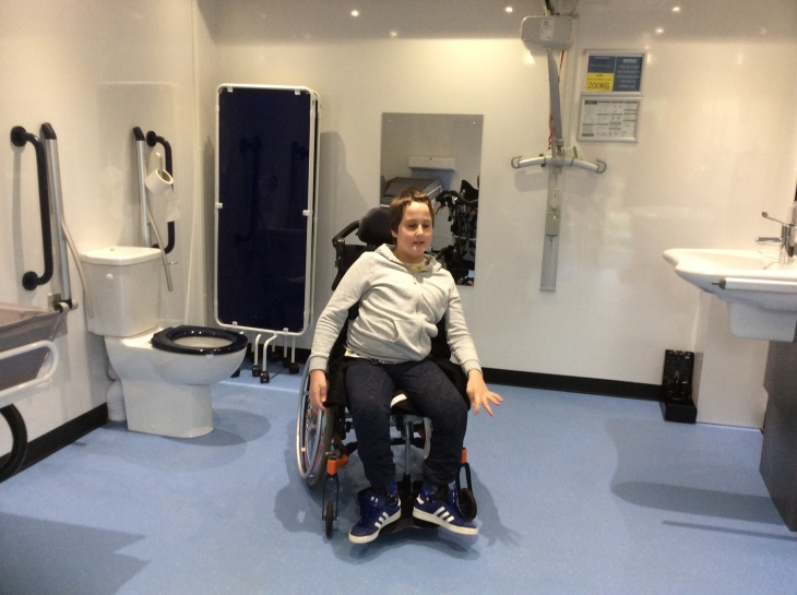 A 12 year old boy, wearing a light grey hoodie and dark grey trousers, using an orange manual wheelchair, is looking happy. To his right is a toilet and changing table, behind him is a dark blue privacy screen, mirror and ceiling hoist. To his left is a height adjustable sink. The floor is light blue in colour.
