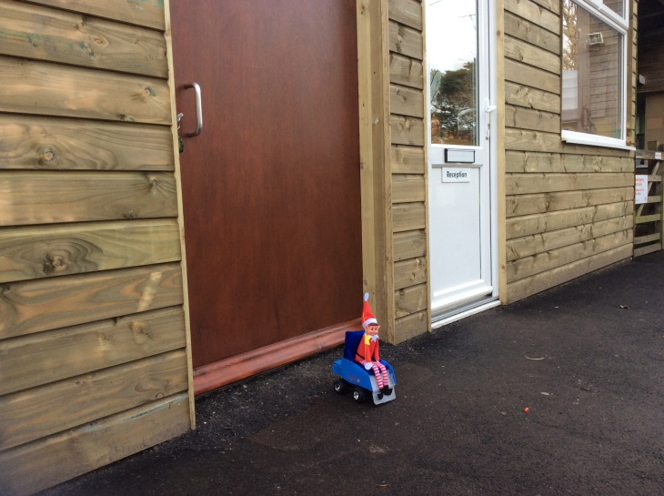 Toy Elf, sat in his powered wheelchair, outside a big wooden door, next to an office with