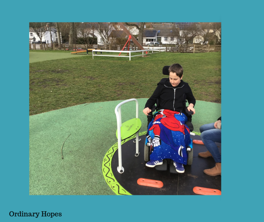 a boy using a powered wheelchair user is enjoying using a wheelchair accessible roundabout.