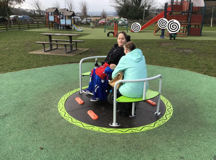 A boy using a powered whelchair is enjoying being on a wheelchair accessible roundabout with his grandma. Several other non-accessible pieces of equipment, including a climbing fort with slide are pictured behind him.