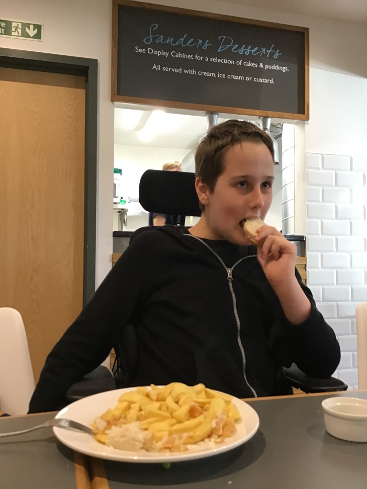12 year old boy, wearing a black zip hoodie is clearly enjoying his fish and chips. Parts of his wheelchair are in sight, armrests and headrest. The sign above hi says