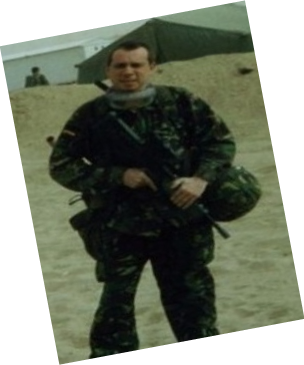 Man dressed in armed forces clothing in a sandy environment with an army tent in the background.