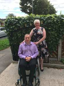 A smarltly dressed and smiling couple pose. The woman is stood behind the man, who is using a wheelchair. SHe is wearing a summery floral dressm the man is wearing black trousers and a lilac shirt.