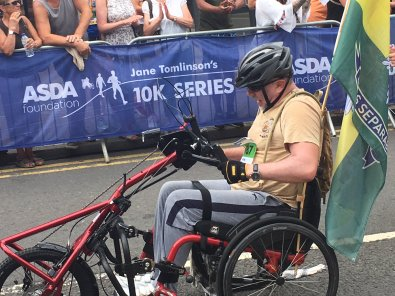 "Man using a hand powered cycle. Man is wearing a grey cycling helmet, light coloured T-shirt and grea trousers. He looks determined. There is what appears to be a forces flag attached to the rear of his cycle. Signs behind him state ""Asda Foundation Jane Tomlinson's 10K series."