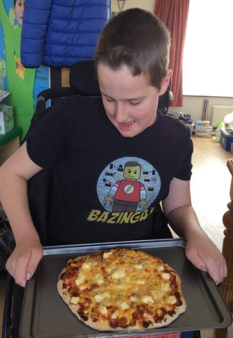 "A boy using a wheelchair is smiling and looking down at his home made pizza. He is wearing a black Tshirt with a Lego Sheldon character on it and the word ""Bazinga!"""