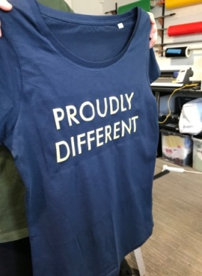 "A dark blue T-shirt with the words ""Proudly Different"" on it."