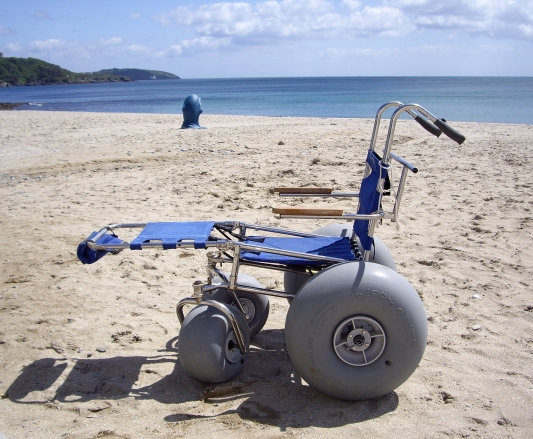 A sand chair on a beach, with the sea behind. It is a basic, upright mesh seatwith leg support extended. Woor armrests on metal poles, no head support, no body support and no lap belt or supportive harness. Large air wheels at the front and huge air wheels at the rear.