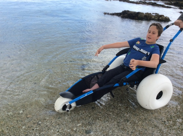 A boy using a Hippocampe beach wheelchair with sand wheels is in the sea. There are little black spots all over the sea. These spots are actually raindrops hitting the sea.