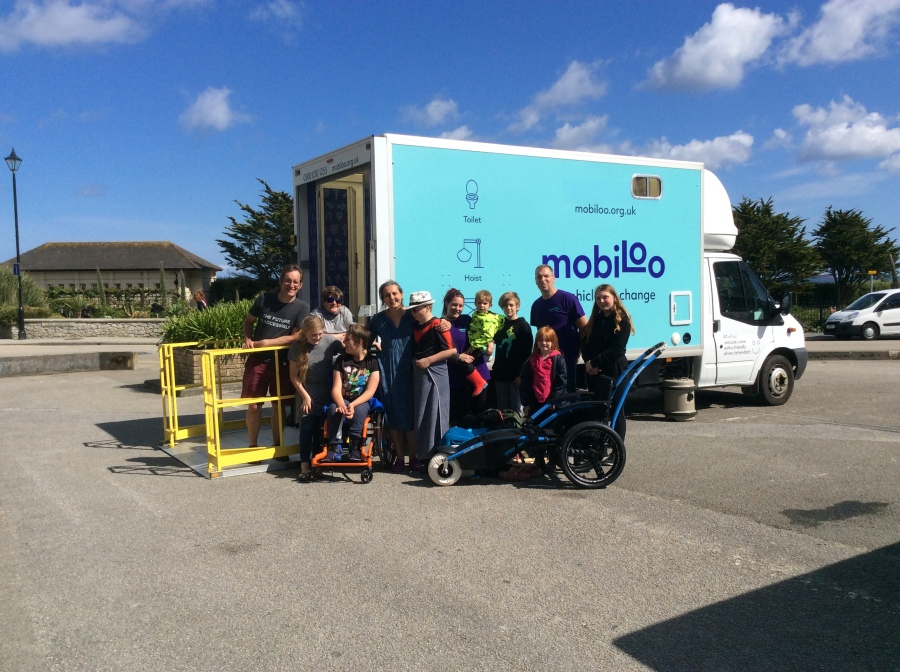A group of people in front of a Mobiloo vehilcle. One boy is using an orange wheelchair, and an unoccupied beach chair is also inthe picture.