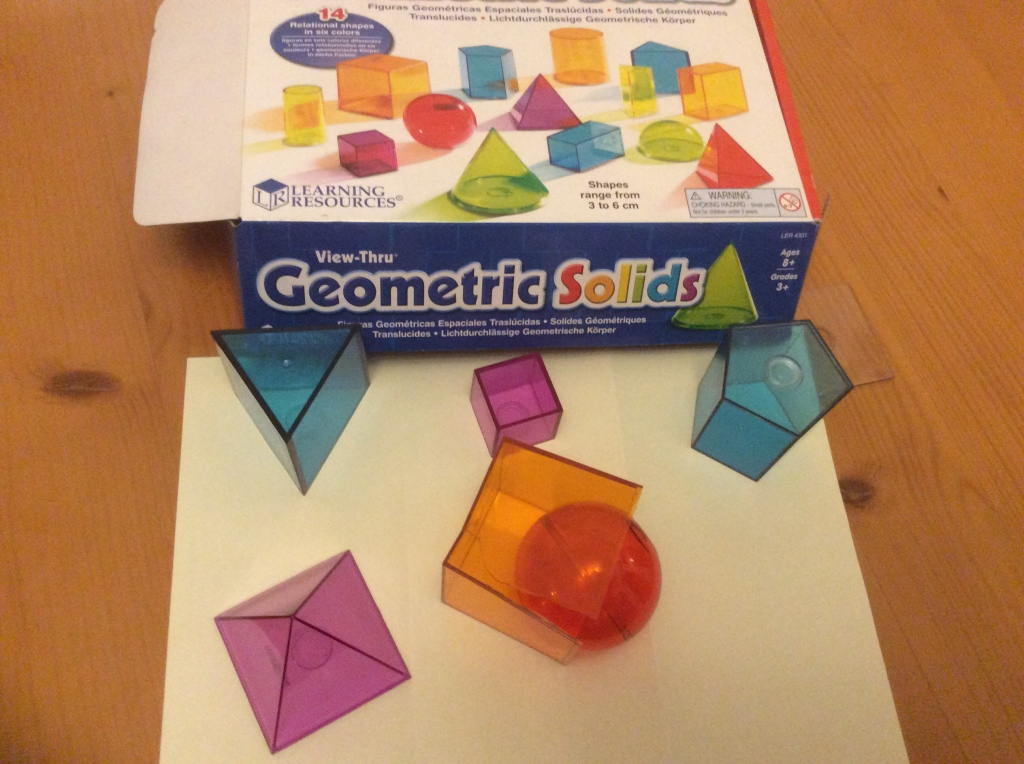 Some brightly coloured plastic geometric solids. A red sphere has been pushed into and orange cube and broken it.